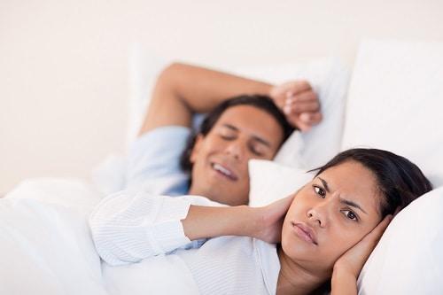 man snoring woman grimacing
